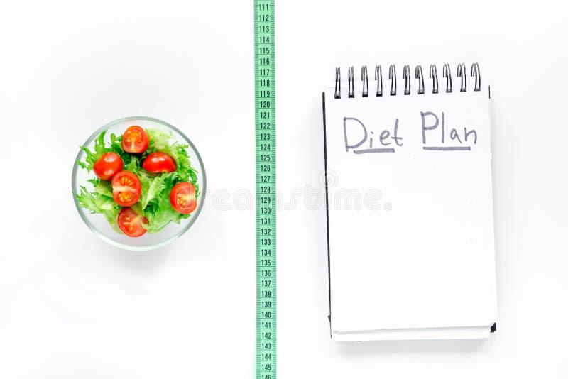 Cuaderno para el plan de la dieta, ensalada con los productos frescos y cinta métrica en la mofa blanca de la opinión superior de imagenes de archivo