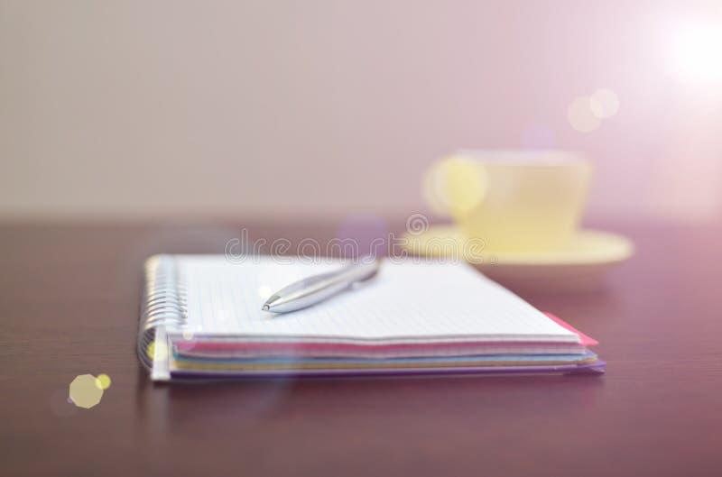 Cuaderno, pluma de acero y amarillo en la tabla con luz del sol imagenes de archivo