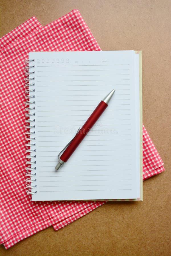 Cuaderno, pluma roja en fondo de madera imagen de archivo