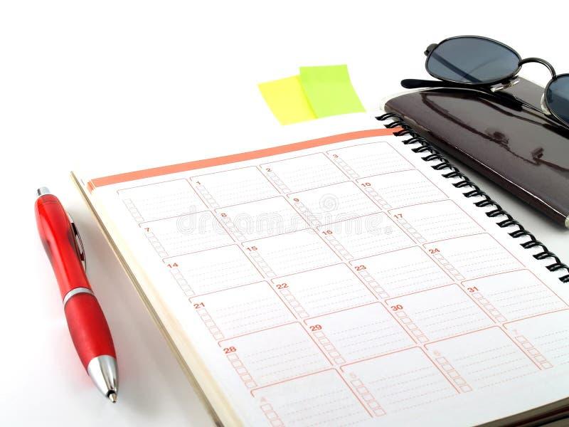 Cuaderno, pluma roja, pasaporte y gafas de sol en el fondo blanco imagenes de archivo