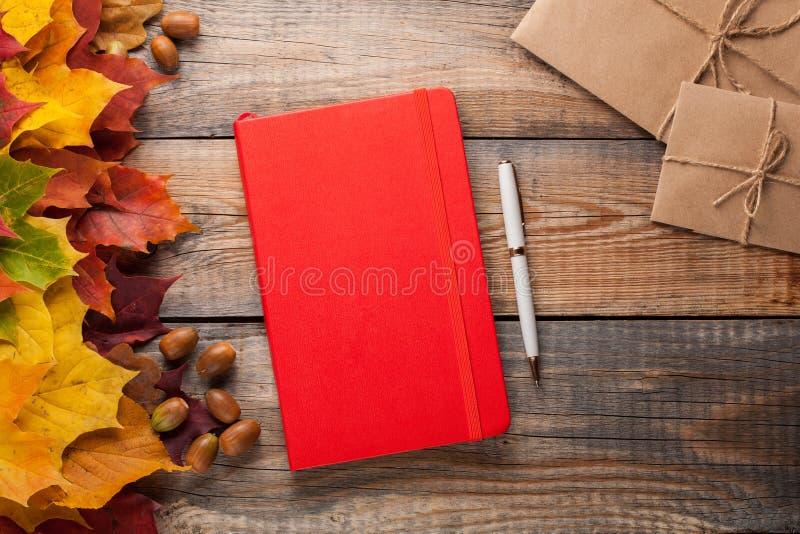 Cuaderno rojo con los sobres de la pluma y del papel en la tabla de madera vieja Hojas de otoño del arce y bellotas mezcladas al  imágenes de archivo libres de regalías