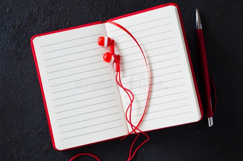 Cuaderno rojo vac?o con la pluma roja y auriculares en fondo oscuro Papel en blanco para el texto foto de archivo libre de regalías