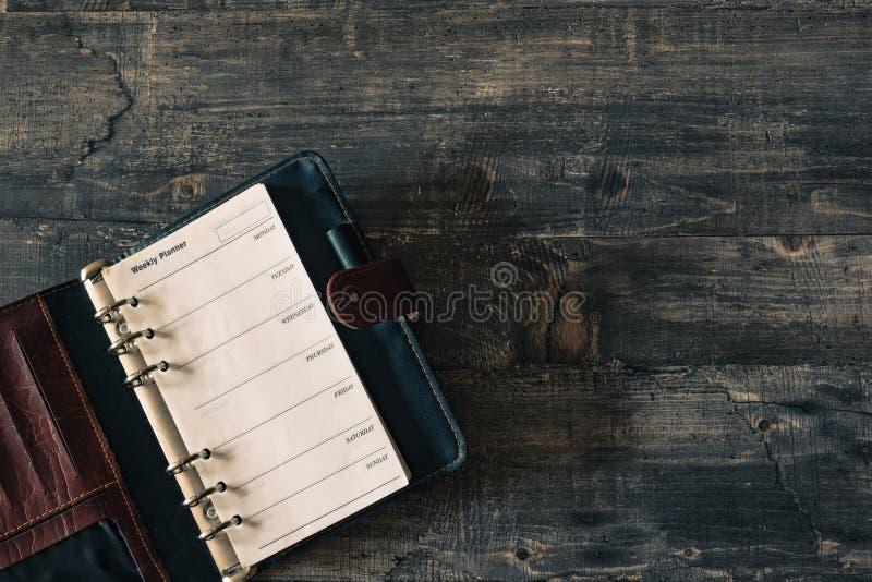 Cuaderno semanal del planificador en el escritorio de madera oscuro fotos de archivo