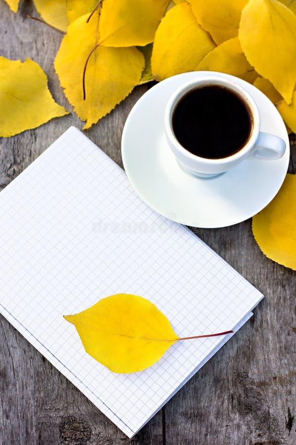 Cuaderno, taza de café y hojas de otoño amarillas imagenes de archivo