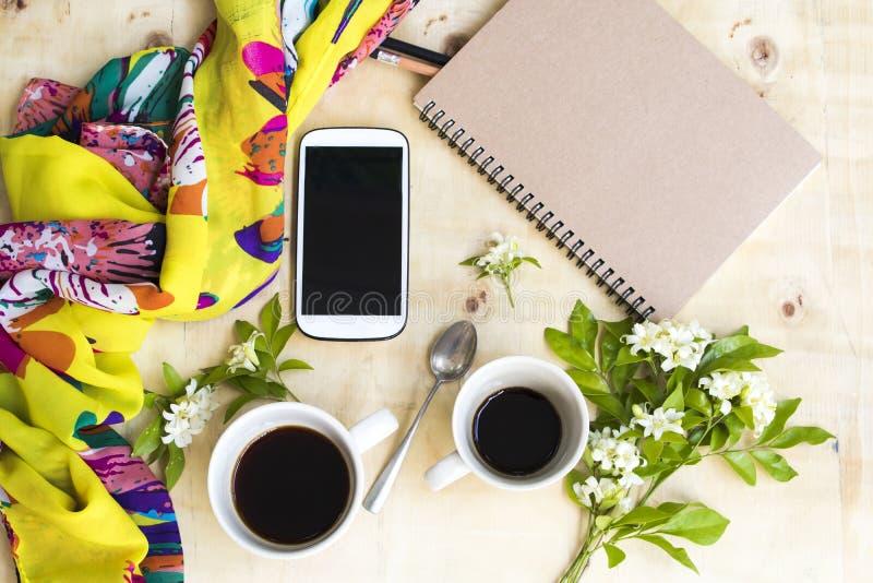 Cuaderno, teléfono móvil para el trabajo del negocio y bufanda amarilla, taza caliente del gemelo del café express del café imágenes de archivo libres de regalías