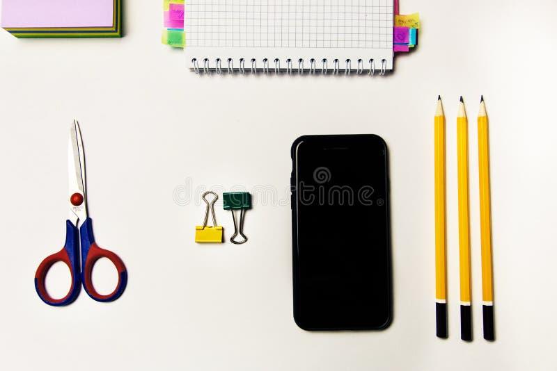 Cuaderno, tijeras, lápices, clips para las hojas y teléfono celular Tema de la oficina imagen de archivo libre de regalías