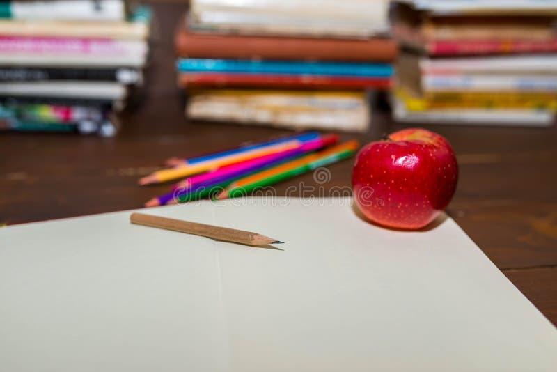 Cuaderno vacío abierto, manzana, lápices del color, libros coloridos en el fondo foto de archivo libre de regalías