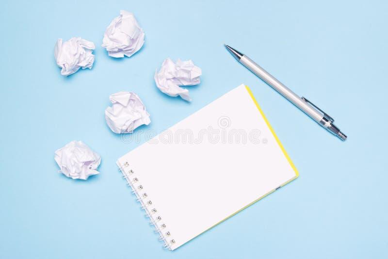 Cuaderno vacío abierto, pluma y bolas de papel arrugadas en fondo de papel azul Proceso de la creación, idea o concepto creativo  foto de archivo
