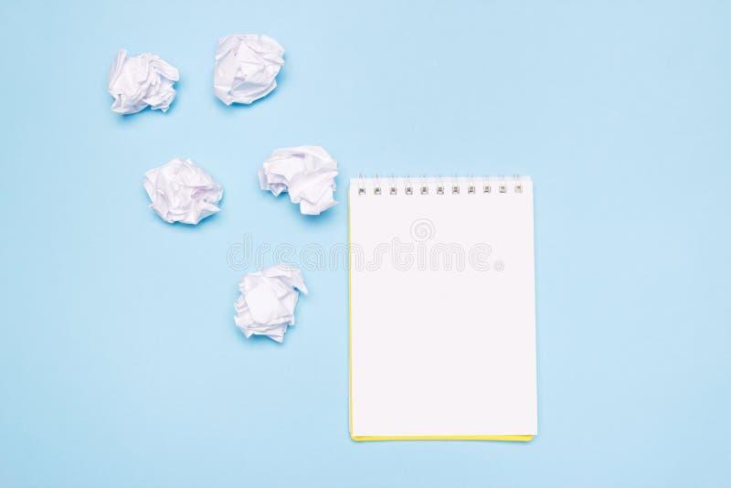 Cuaderno vacío abierto y bolas de papel arrugadas en fondo de papel azul Proceso de la creación, idea o concepto creativo de las  imagen de archivo libre de regalías