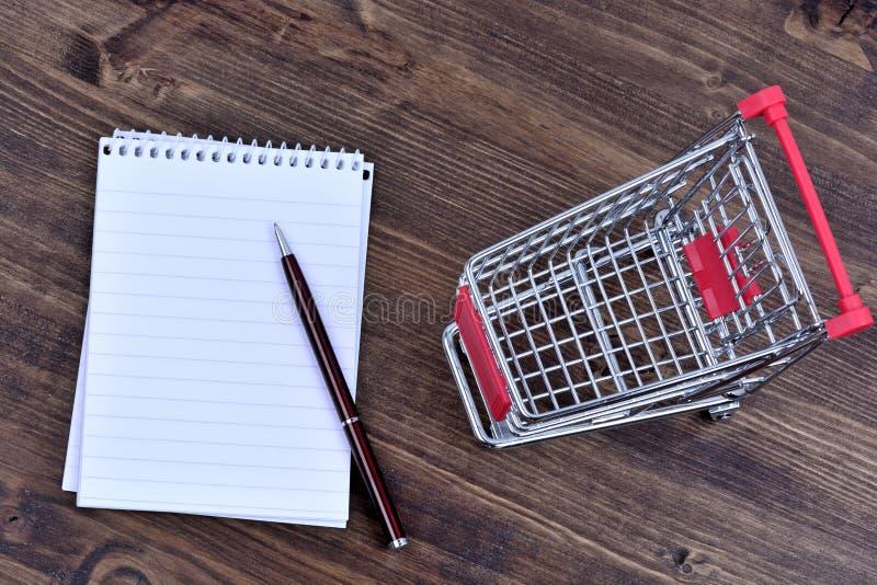 Cuaderno vacío con el carro de la compra en la tabla fotografía de archivo libre de regalías