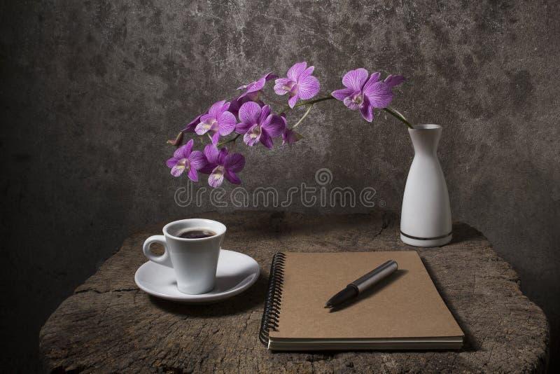 cuaderno vacío con la taza de café y la orquídea púrpura en florero en imagen de archivo