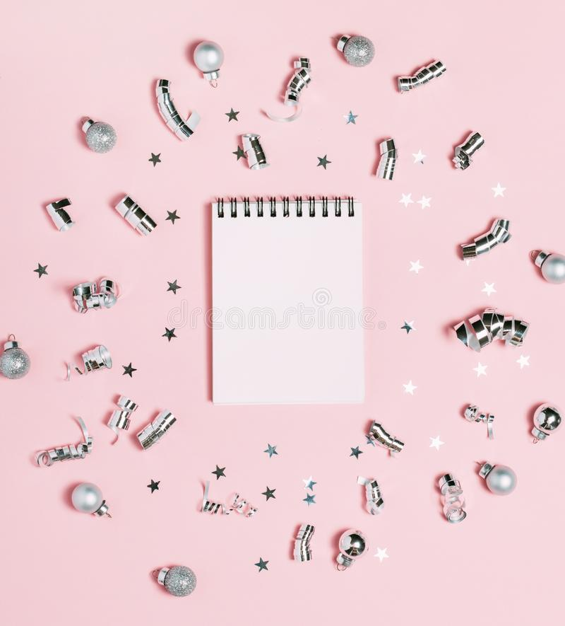 Cuaderno vacío en fondo rosado con la decoración de plata de la Navidad brillante y festivo Concepto del Año Nuevo, visión superi imagen de archivo libre de regalías