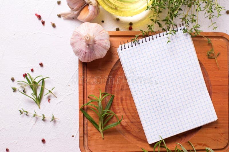 Cuaderno vacío para las recetas con las hierbas y las especias frescas foto de archivo