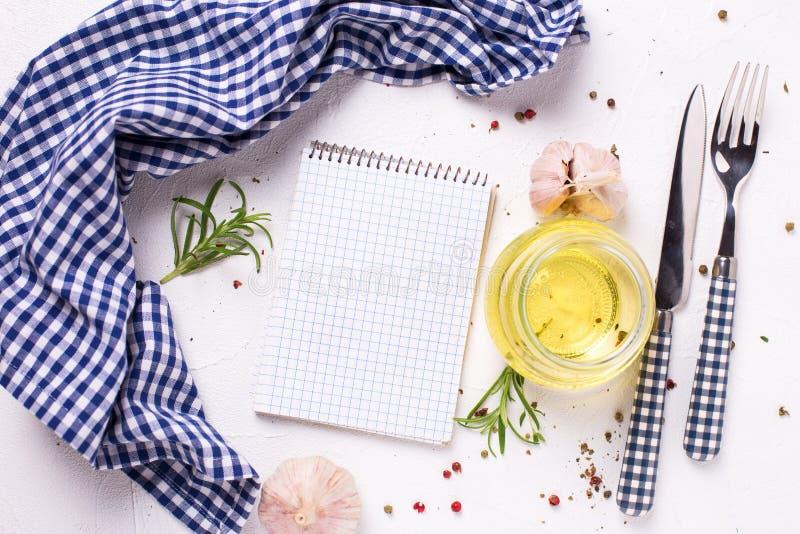 Cuaderno vacío para las recetas con las hierbas y las especias frescas a bordo en el fondo texturizado ligero, visión superior Fo fotos de archivo