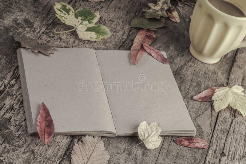 Cuaderno y café en la tabla de madera adornada con las hojas secadas fotos de archivo libres de regalías