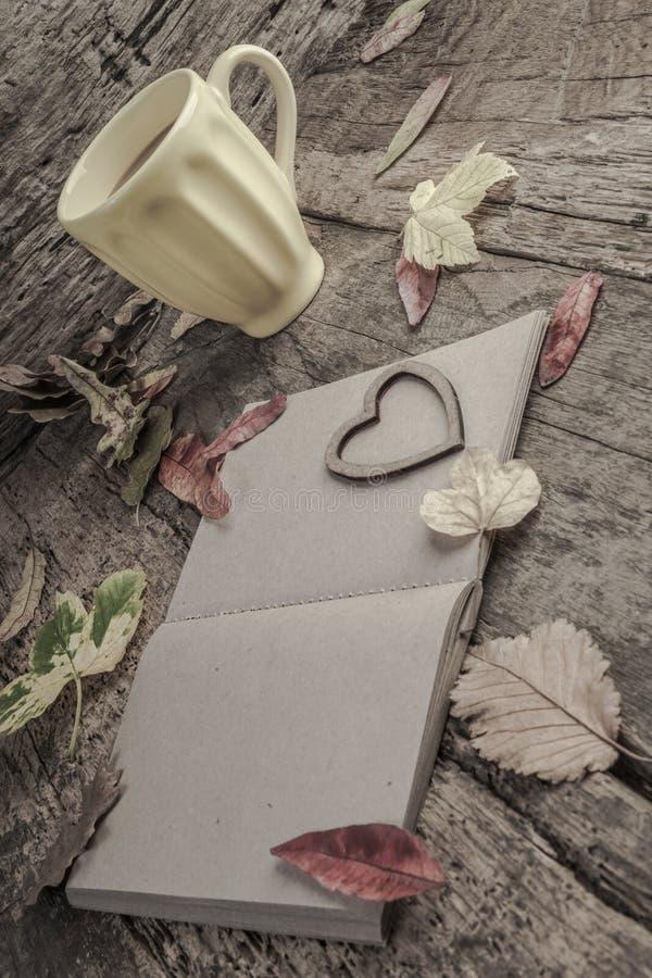 Cuaderno y café en la tabla de madera adornada con las hojas secadas foto de archivo libre de regalías