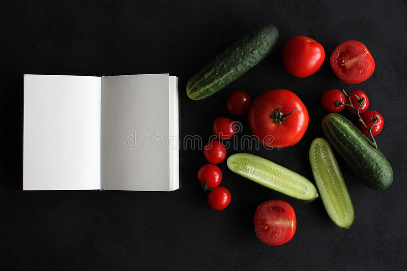 Cuaderno y composición de verduras en el escritorio de madera negro imagen de archivo