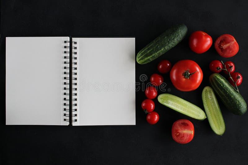 Cuaderno y composición de verduras en el escritorio de madera negro imágenes de archivo libres de regalías