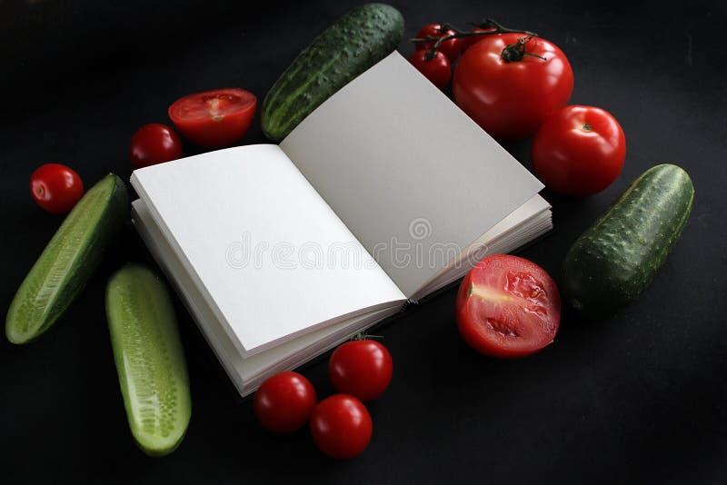 Cuaderno y composición de verduras en el escritorio de madera negro fotografía de archivo libre de regalías