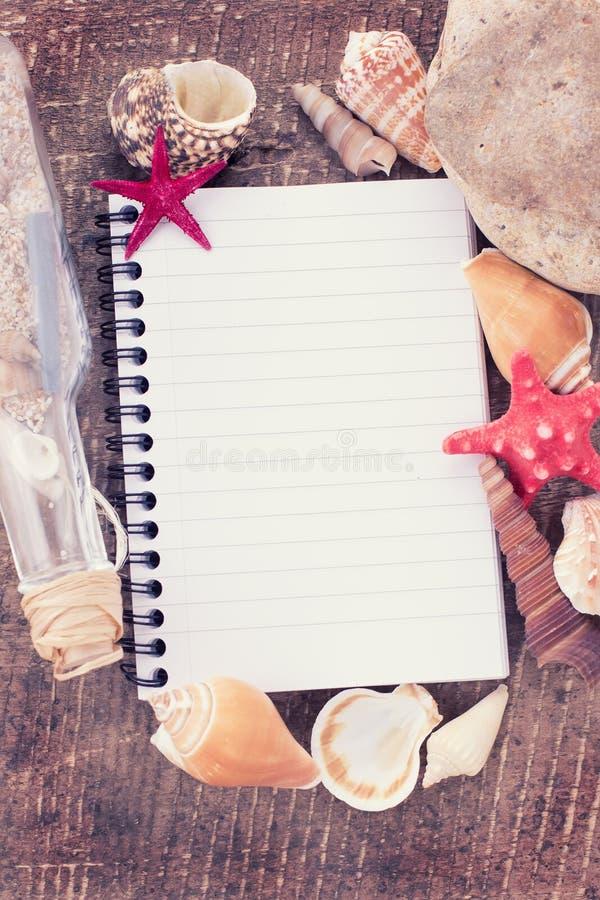 Cuaderno y conchas marinas en fondo de madera imagen de archivo
