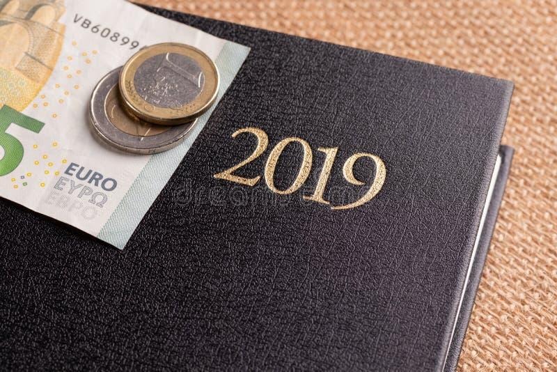 Cuaderno y dinero en la tabla Billetes de banco de la libreta y del euro El concepto de planificación de empresas, viaje, costos  imagen de archivo