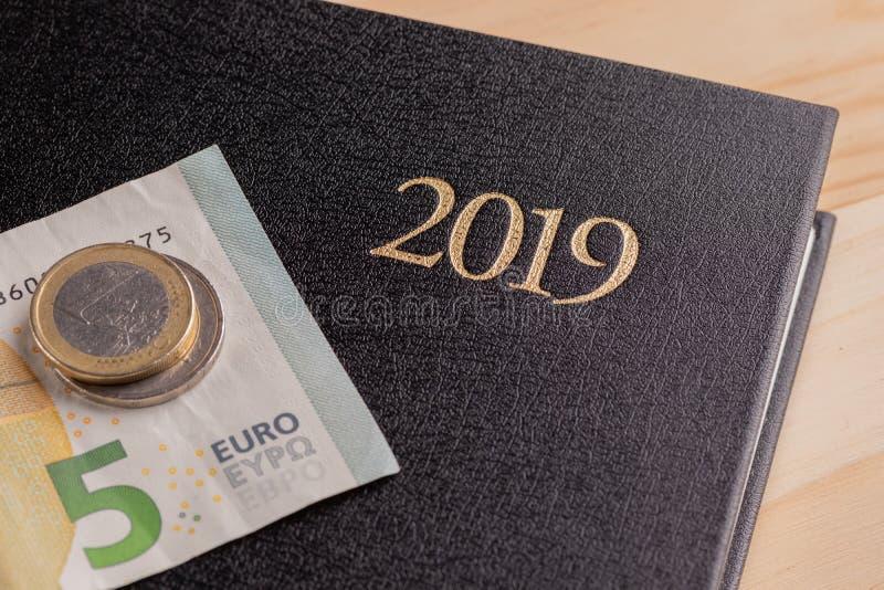 Cuaderno y dinero en la tabla Billetes de banco de la libreta y del euro El concepto de planificación de empresas, viaje, costos  fotografía de archivo libre de regalías