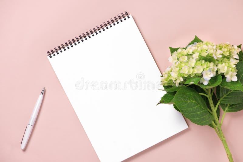 Cuaderno y flores de la visión superior en la mesa Para casarse el plann imagen de archivo