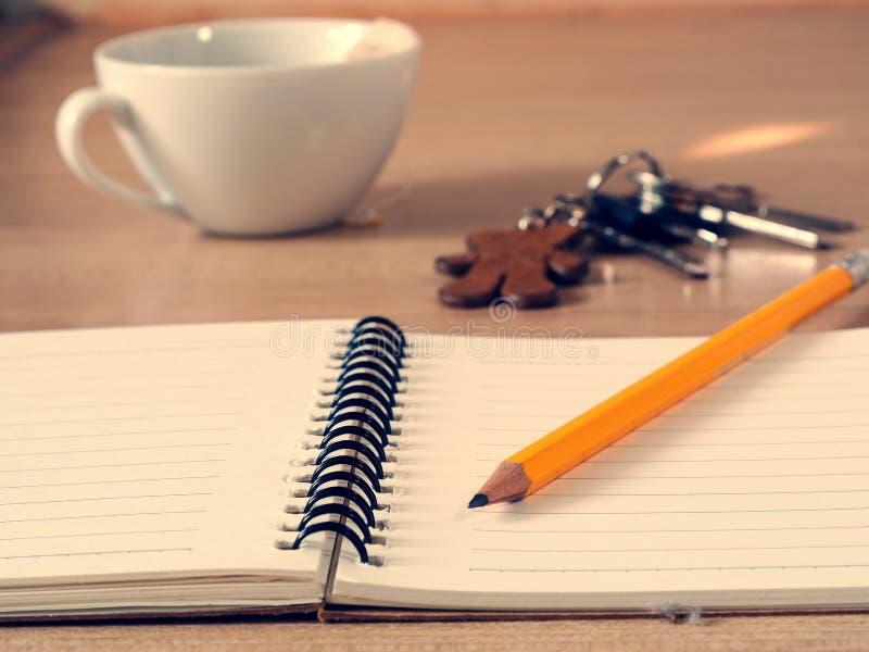 Cuaderno y lápiz con una taza de fondo del té foto de archivo