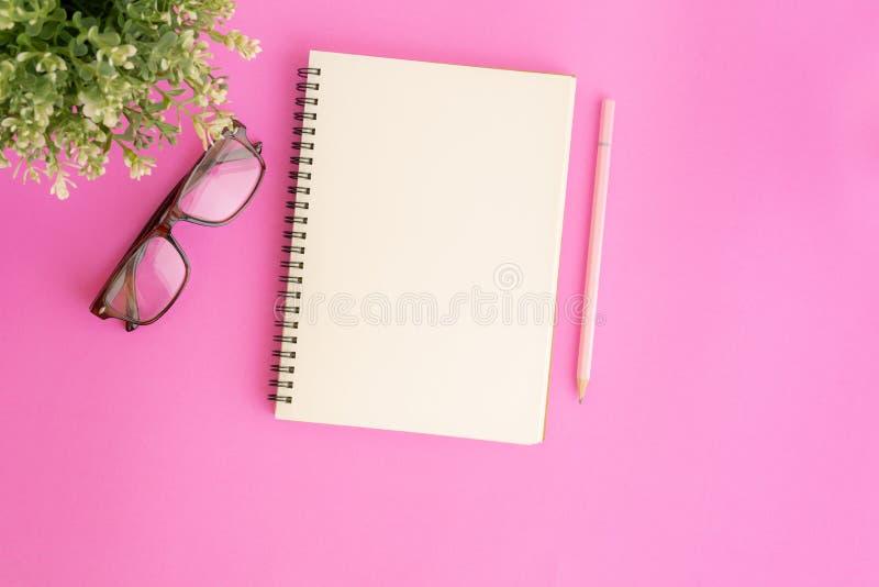 Cuaderno y lápiz en blanco en el fondo rosado, foto puesta plana del cuaderno para su mensaje fotos de archivo
