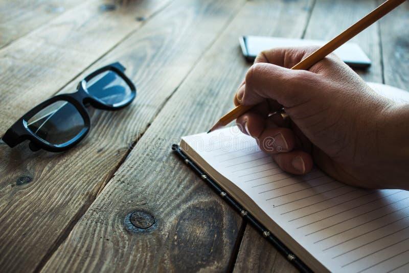 Cuaderno y lápiz en la mano de un hombre y de vidrios en bacground de madera fotos de archivo libres de regalías
