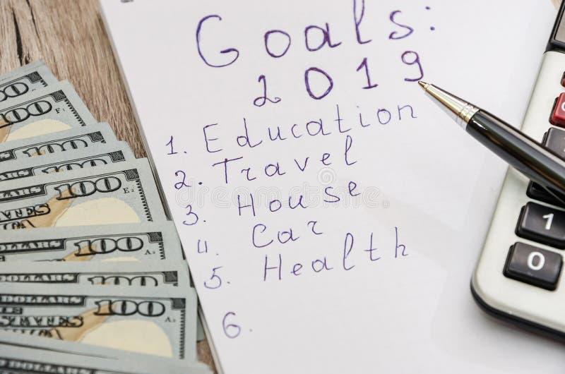 Cuaderno y pluma blanca, calculadora y dólares de primer en fondo de madera fotos de archivo