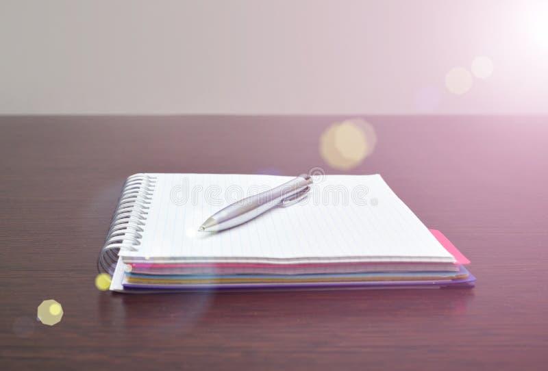 Cuaderno y pluma de acero en la tabla con luz del sol foto de archivo