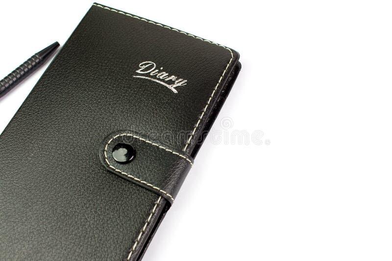 Cuaderno y pluma de cuero negros en el fondo blanco fotografía de archivo