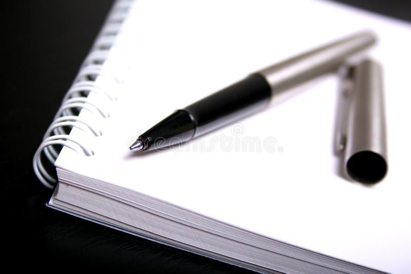 Cuaderno y pluma en blanco imagenes de archivo