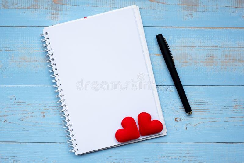 Cuaderno y pluma en blanco con la decoración roja de la forma del corazón de los pares en fondo de madera azul de la tabla El cas foto de archivo libre de regalías
