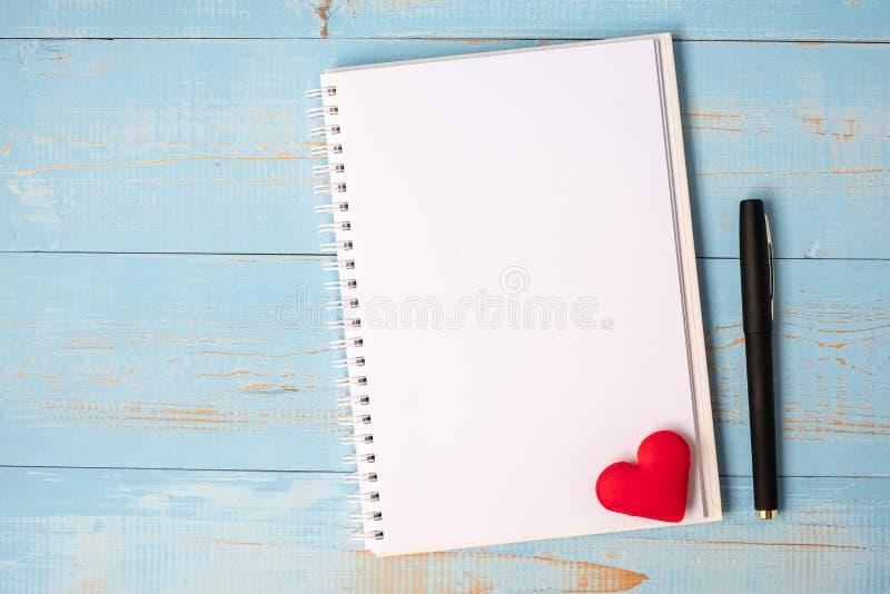 Cuaderno y pluma en blanco con la decoración roja de la forma del corazón de los pares en fondo de madera azul de la tabla El cas foto de archivo