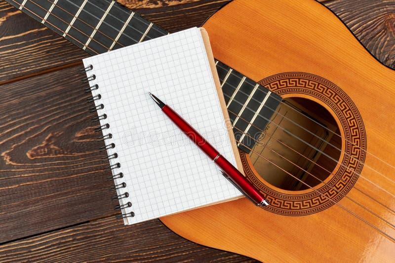 Cuaderno y pluma en blanco en la guitarra fotos de archivo