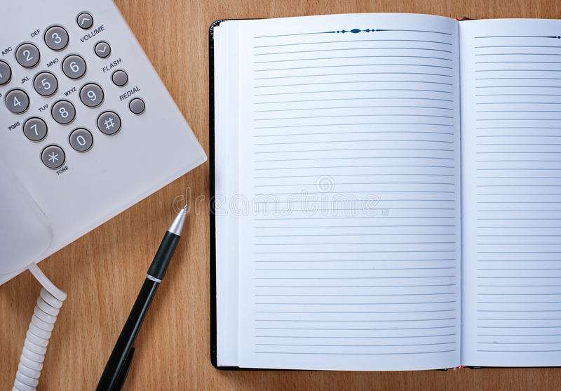 Cuaderno y pluma en la telefonista Table fotografía de archivo
