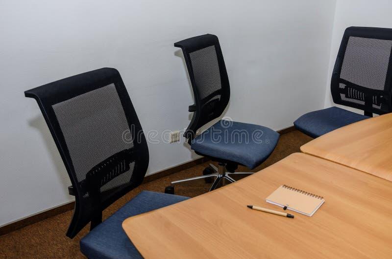 Cuaderno y pluma en un escritorio de oficina Tabla y sillas en la oficina Sala de conferencias en la oficina imagen de archivo libre de regalías