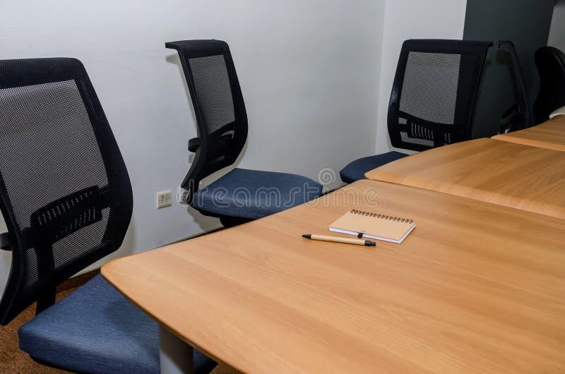 Cuaderno y pluma en un escritorio de oficina Tabla y sillas en la oficina Sala de conferencias en la oficina foto de archivo libre de regalías