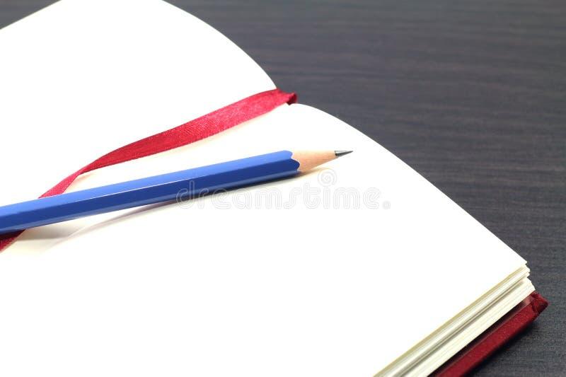 Cuaderno y pluma marrón en la tabla de madera foto de archivo