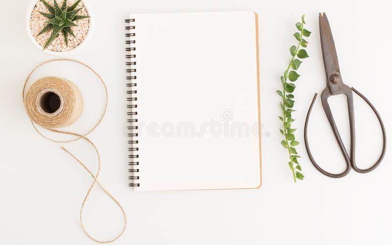 Cuaderno y tijeras en blanco en el fondo blanco, la imagen de la visión superior del cuaderno blanco y el espacio vacío para el t fotografía de archivo libre de regalías
