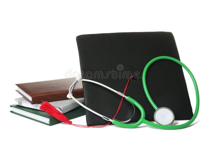 Cuadernos del estetoscopio y sombrero de la graduación en blanco Materia de los estudiantes de medicina imagen de archivo libre de regalías
