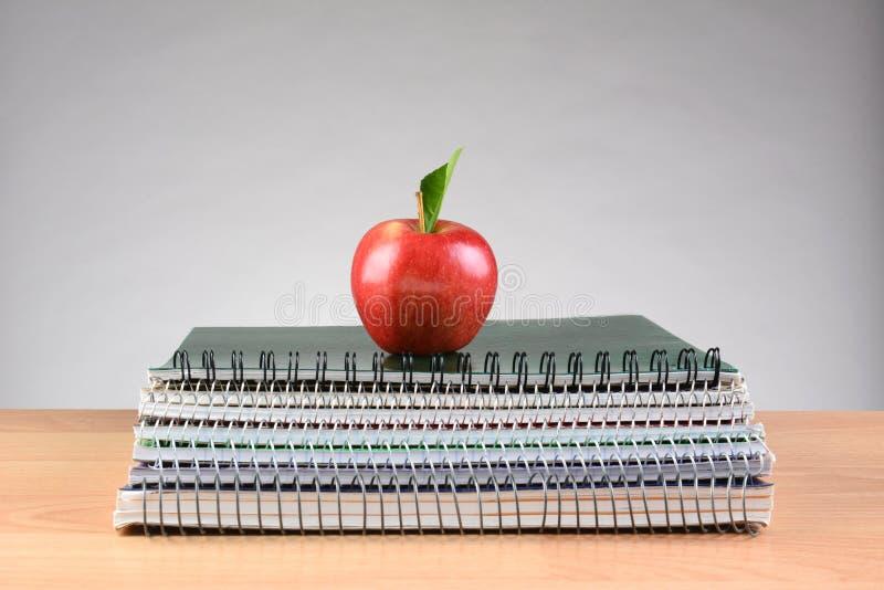 Cuadernos espirales y Apple rojo imágenes de archivo libres de regalías