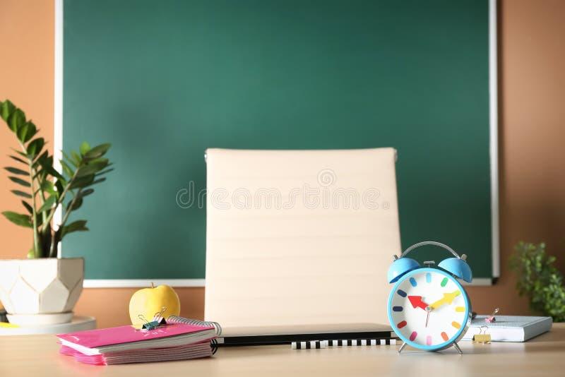 Cuadernos, manzana y despertador en la tabla imagenes de archivo