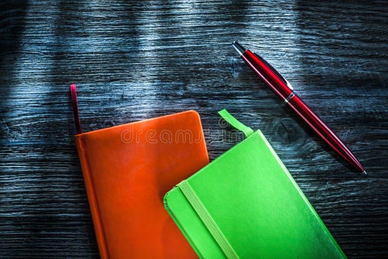 Cuadernos verdes y anaranjados en el tablero de madera fotografía de archivo libre de regalías