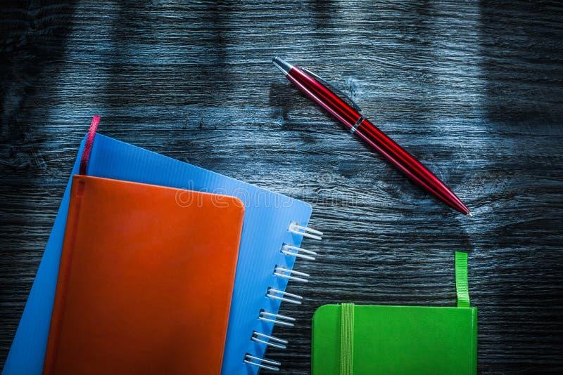 Cuadernos verdes y anaranjados en el tablero de madera imagenes de archivo