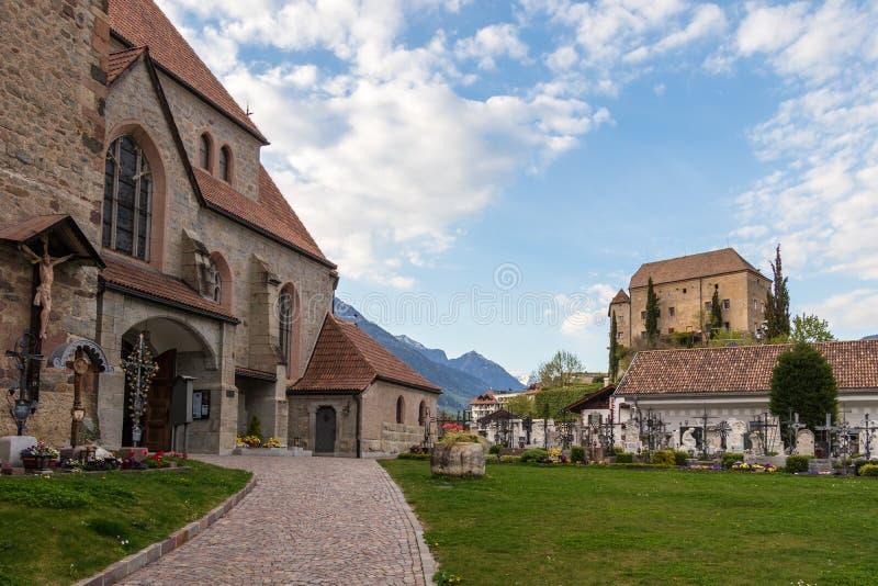 Cuadrado de la entrada a la iglesia vieja, Alte Kirche, con el cementerio y el castillo Schenna en el fondo Scena, el Tyrol del s imagenes de archivo