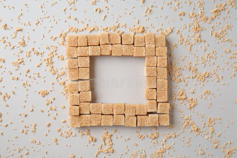 Cuadrado hecho de los cubos marrones del azúcar de caña en fondo ligero fotos de archivo