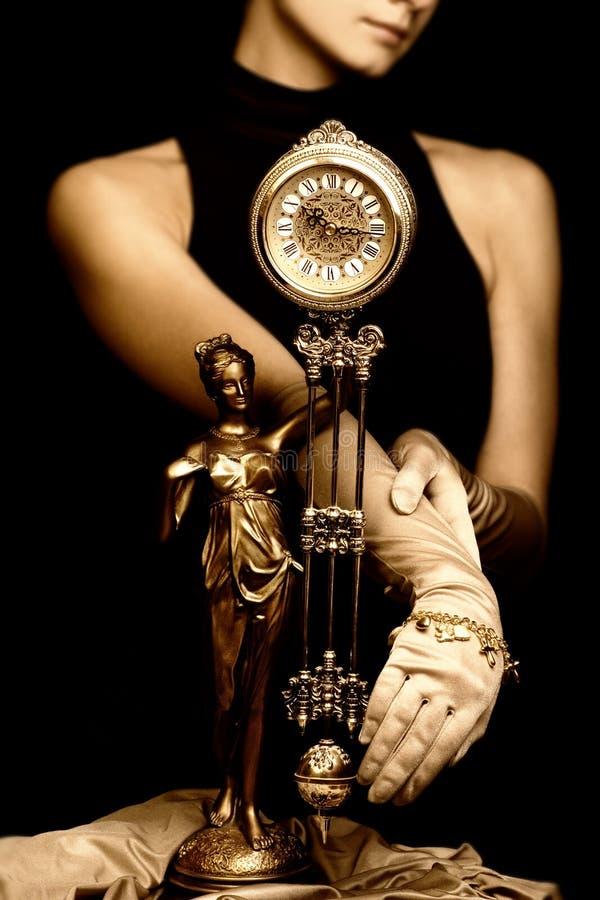 Cuadro de la sepia de un reloj y de una chica joven hermosa (foco en cloc fotografía de archivo libre de regalías